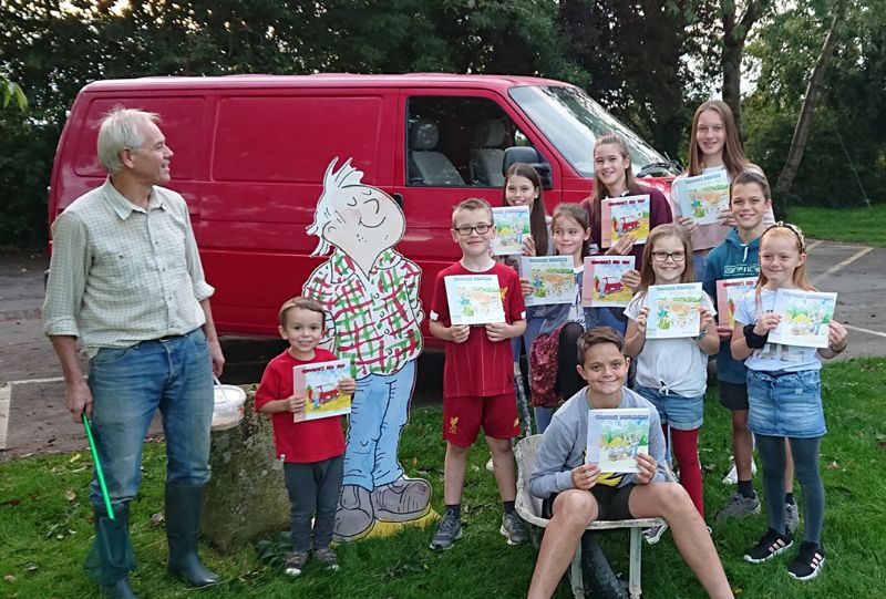 John with Grandad from the books and ten of his grandchildren.   Right to left, Back row - Sophie, Ella and Katie Smart. Middle row – James Carter and Lucy Smart. Front row – Charlotte, Sienna, Lewis and Max Carter. Henry Carter is in the wheelbarrow (18 month old Amelia Carter wouldn't stand still)