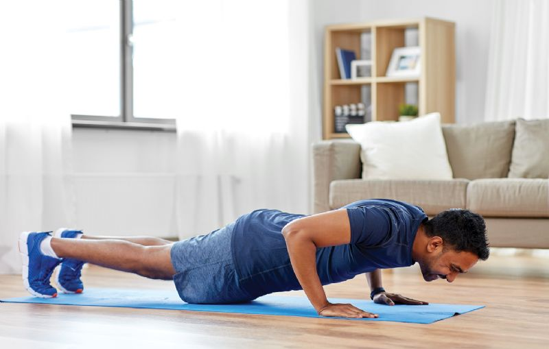 Man doing press ups in living room home workout fitness