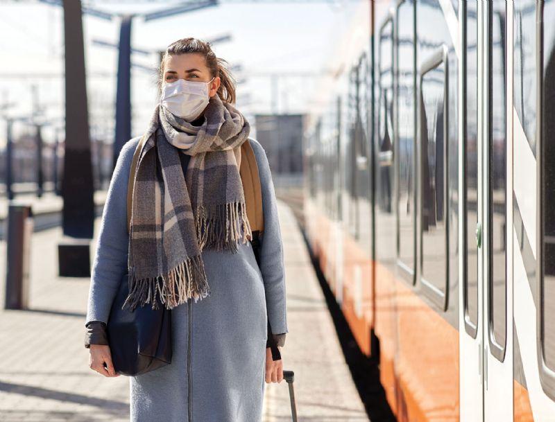 Woman wearing face mask in public train station